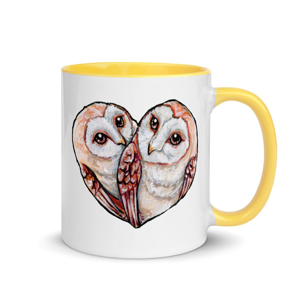 An 11 oz white ceramic mug with yellow trim, printed with two barn owls close together forming the shape of a heart.