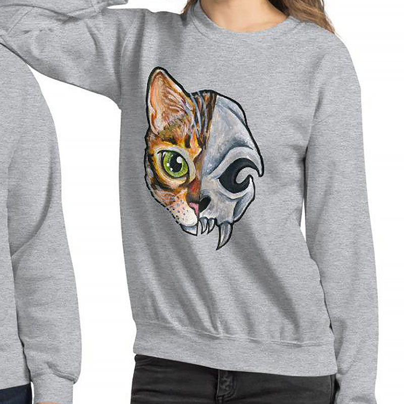 A woman is wearing a unisex sweatshirt in the colour sport grey, printed with art split into two: the left side features the face of a bengal cat, and the right side features an evil looking cat skull.