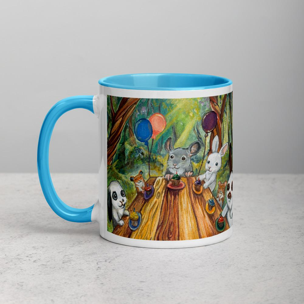 An 11 oz ceramic coffee mug, with blue trim, printed with art of a cupcake party with three rabbits, two hamsters and a chinchilla in the forest