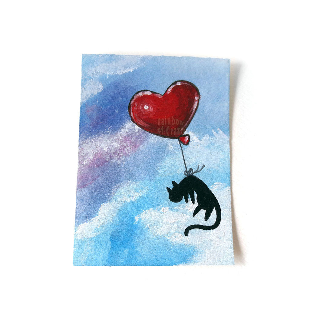 An ACEO painting of a black cat floating through a blue and purple sky, tied to a red heart balloon