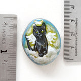 "A beach stone with art of a green eyed black cat as an angel, next to two rulers to show its size: 1 5/16"" x 1 1/8"" or 3.4 cm x 2.8 cm and weighs 0.6 ounces or 17.1 grams"