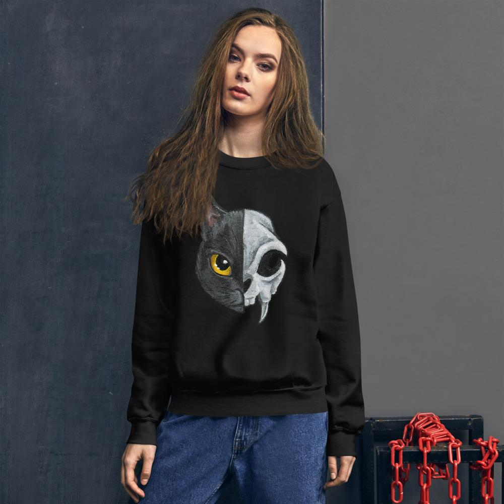 A woman is wearing a unisex sweatshirt in the colour black, printed with a graphic of a split image: the left side features a yellow eyed black cat, and the right side features an evil looking cat skull