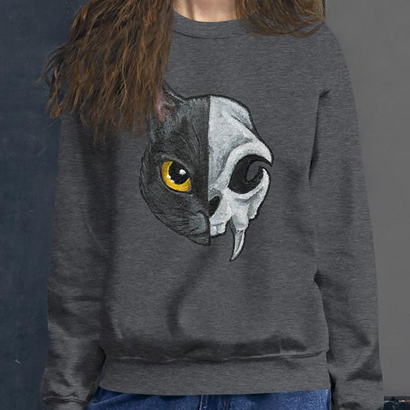 A woman is wearing a unisex sweatshirt in the colour dark heather grey, printed with art of a split image: the left side features a yellow eyed black cat, and the right side features an evil looking cat skull