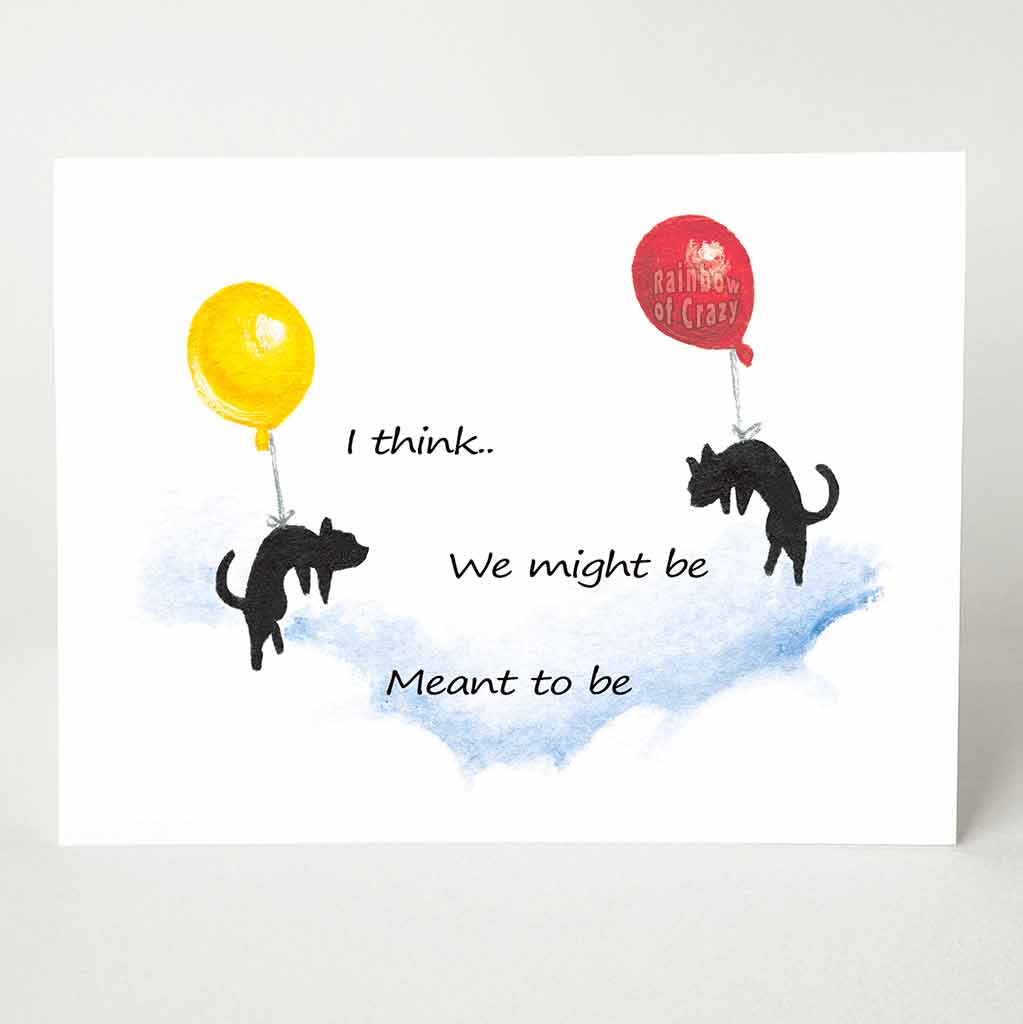 "A greeting card printed with two black cats, each attached to a big balloon, floating in the sky towards each other. The text reads, ""We might be Meant to be"""
