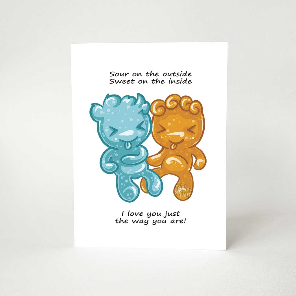"A greeting card with art of two sour candies in the shape of people (one blue, one orange), the card reads, ""Sour on the outside / Sweet on the inside / I love you just the way you are!"""