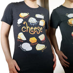 A woman is wearing the Cheese Lovers Unisex Premium T-shirt in dark grey heather, which includes art of 10 styles of cheese.