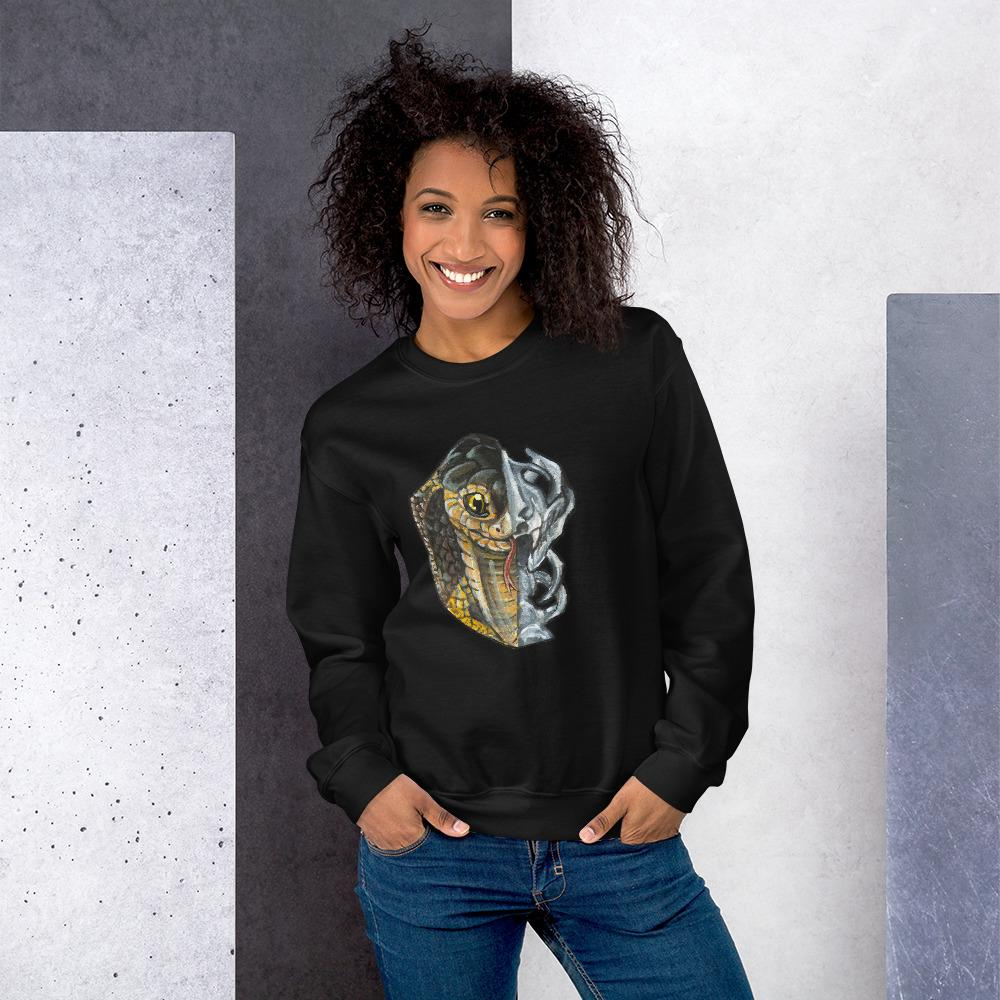 A woman is wearing a unisex sweatshirt in the colour black, printed with an illustration split into two: the left side features the face of a cobra snake, and the right side features an evil looking snake skull.