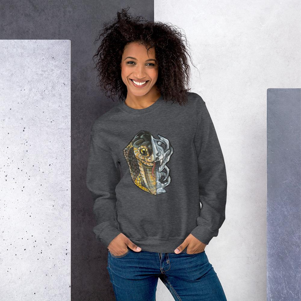 A woman is wearing a unisex sweatshirt in the colour dark heather grey, printed with a graphic split into two: the left side features the face of a cobra snake, and the right side features an evil looking snake skull.