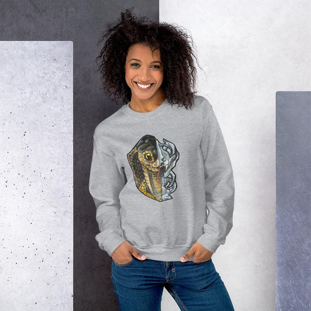 A woman is wearing a unisex sweatshirt in the colour sport grey, printed with an illustration split into two: the left side features the face of a cobra snake, and the right side features an evil looking snake skull.