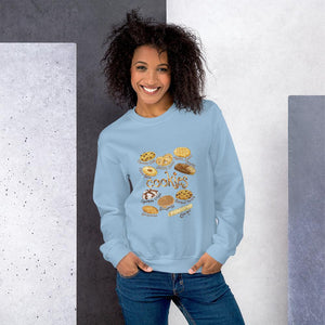 A woman wearing the Cookie Lovers Unisex Sweatshirt in the colour light blue, which features an illustration of 10 types of cookies