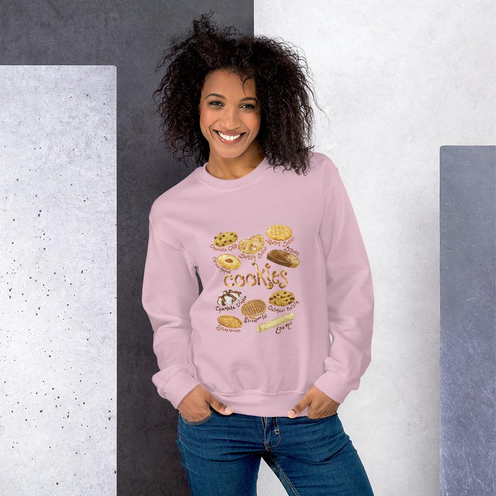 A woman wearing the Cookie Lovers Unisex Sweatshirt in the colour light pink, which features artwork of 10 types of cookies