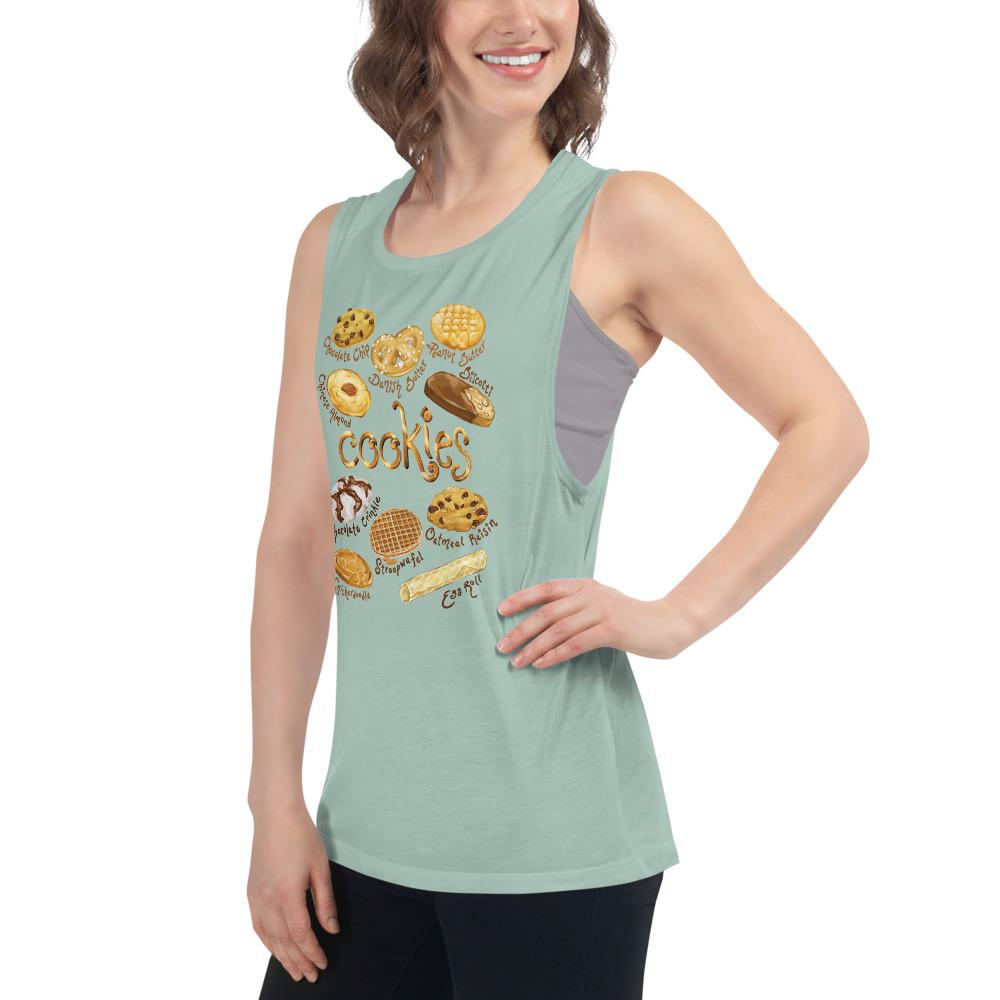 A woman is wearing the Cookie Lovers Women's Muscle Tank Top in the colour dusty blue, which is printed with a graphic of 10 different types of cookies