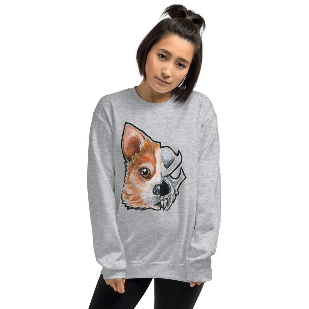 A woman is wearing a unisex sweatshirt in the colour sport grey, which is printed with a split graphic: the left side features the face of a corgi dog, and the right side features an evil looking skull