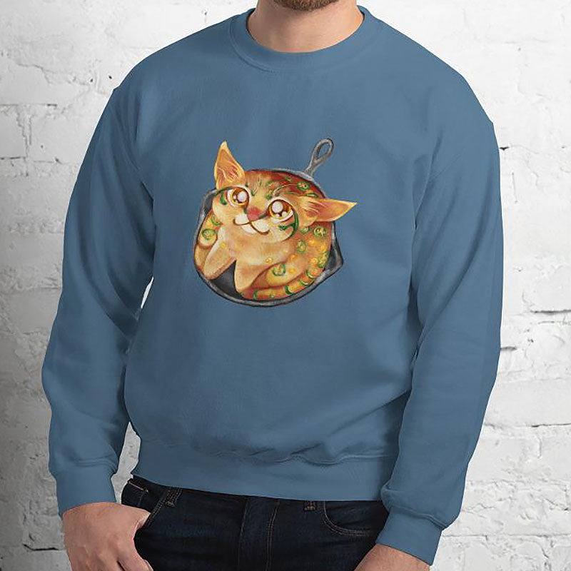 A man is wearing a unisex sweatshirt in the colour indigo blue, featuring art of a cornbread cat with jalapenos, sitting in a cast iron pan.