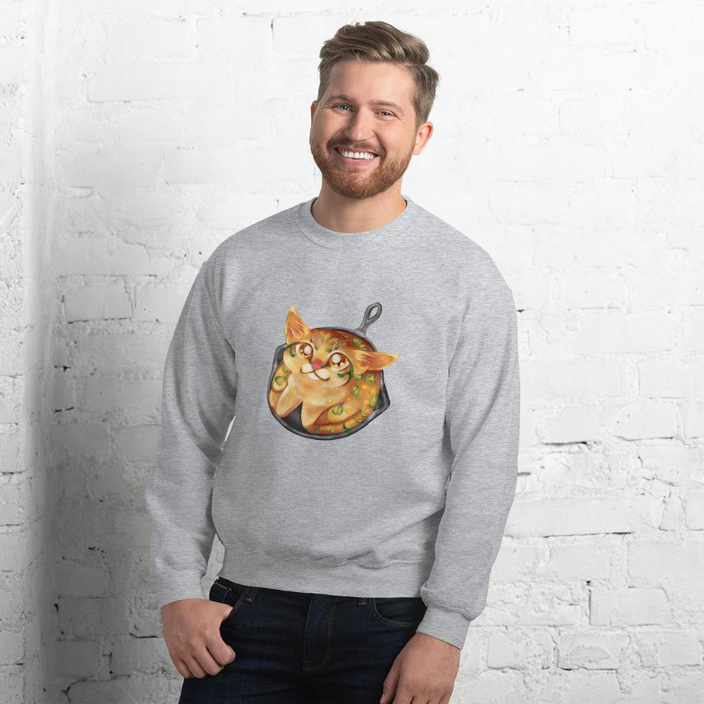A man is wearing a unisex sweatshirt in the colour sport grey, featuring an illustration of a cornbread cat with jalapenos, sitting in a cast iron pan.