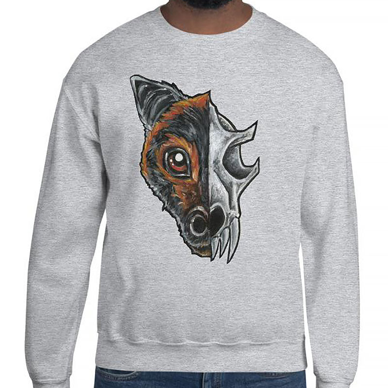 A man is wearing a unisex sweatshirt in the colour sport grey, which is printed with a split illustration: the left side features the face of a flying fox bat, and the right side features an evil looking bat skull
