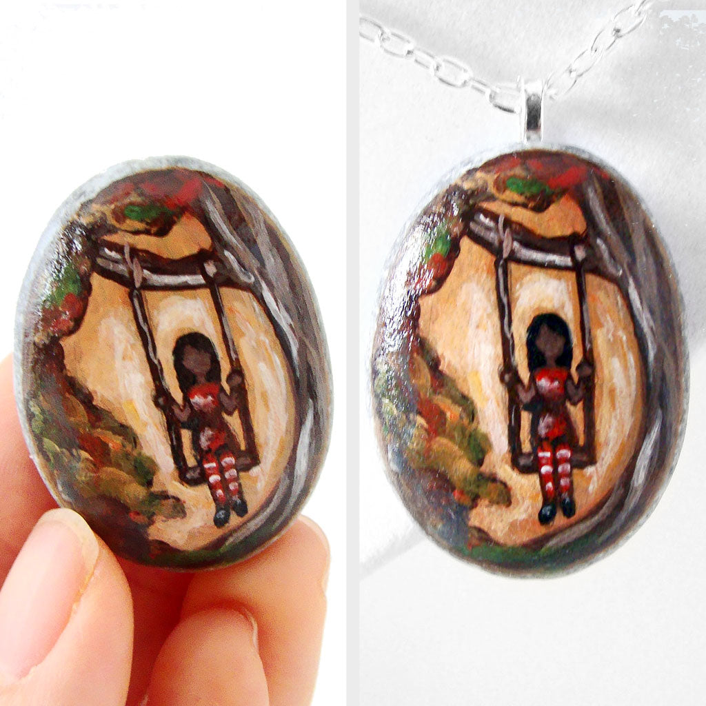 small rock art: a beach stone is hand painted with a girl in red, sitting on a tree swing, available as either a keepsake or a necklace