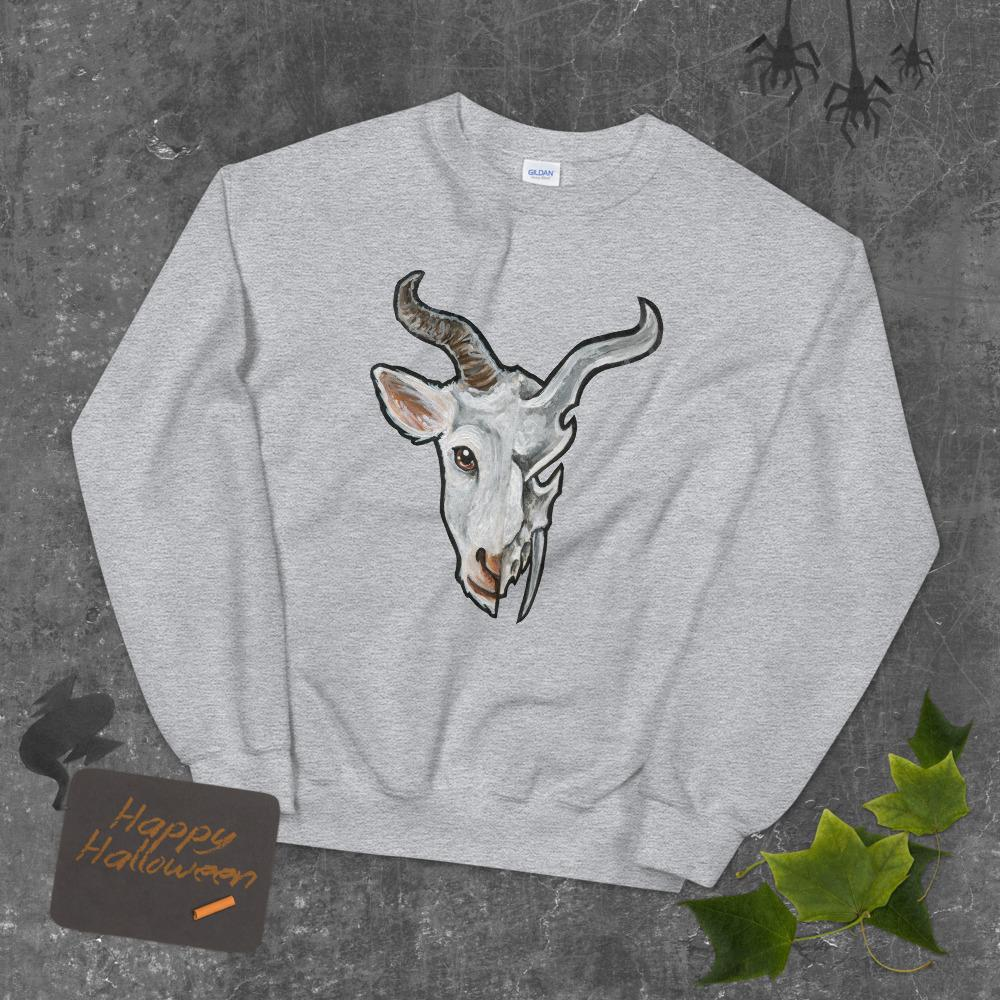 A unisex sweatshirt in the colour sport grey, printed with art of a split image: the left side features the face of a goat, and the ride side features an evil looking goat skull