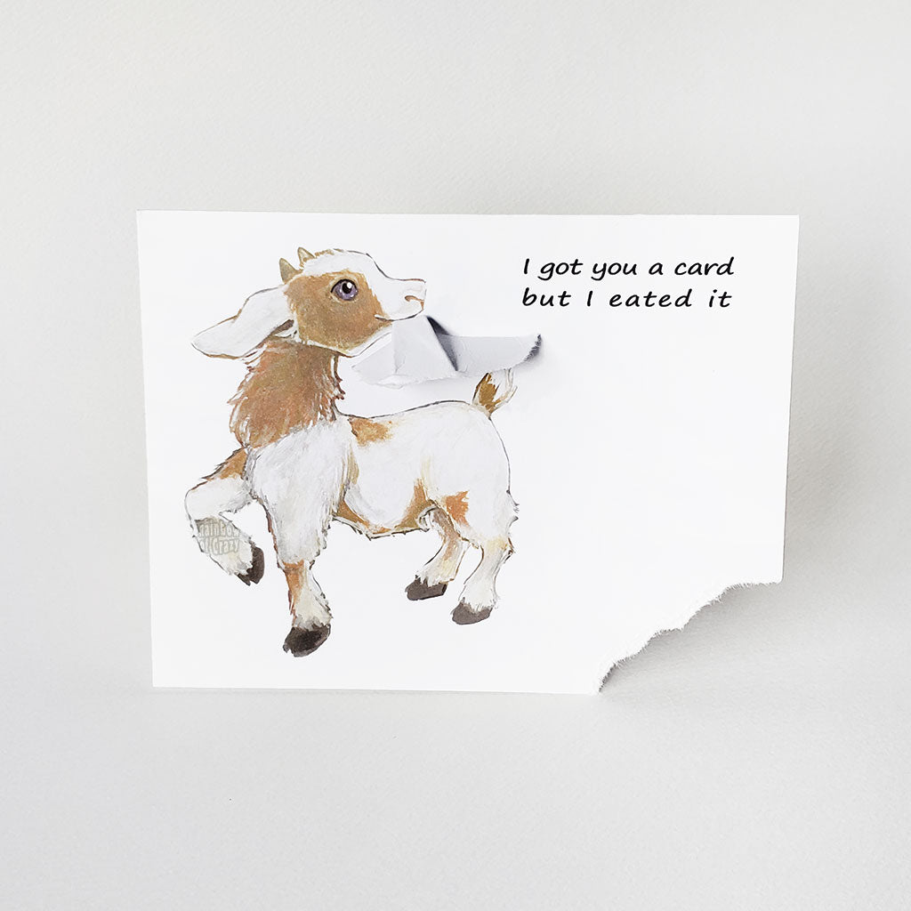 "a funny greeting card with a goat on the front, with the bottom right corner of the card ripped and hanging from its mouth. the card reads, ""I got you a card and I eated it"""