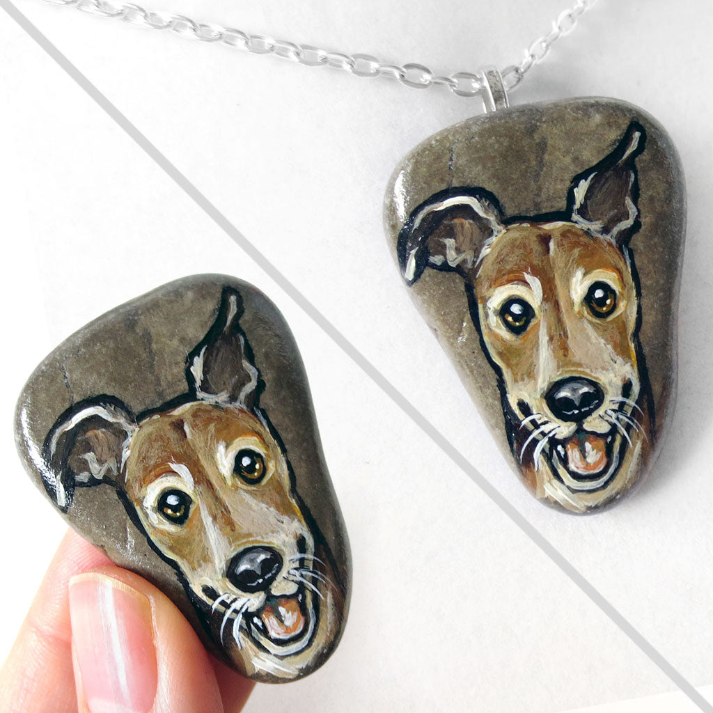 a beach rock painted with art of a close-up of a brown greyhound smiling, available as a stone or necklace