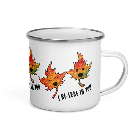"I Believe in You Leaf Enamel Mug holds 12 oz and features two smiling maple leaves and the words, ""I be-leaf in you"". The leaves appear three times around the mug"