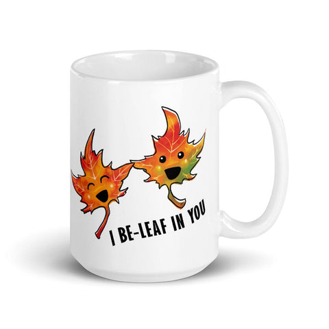 "An 15 oz white ceramic mug, printed with art of two maple leaves, and the words. ""I be-leaf in you"""