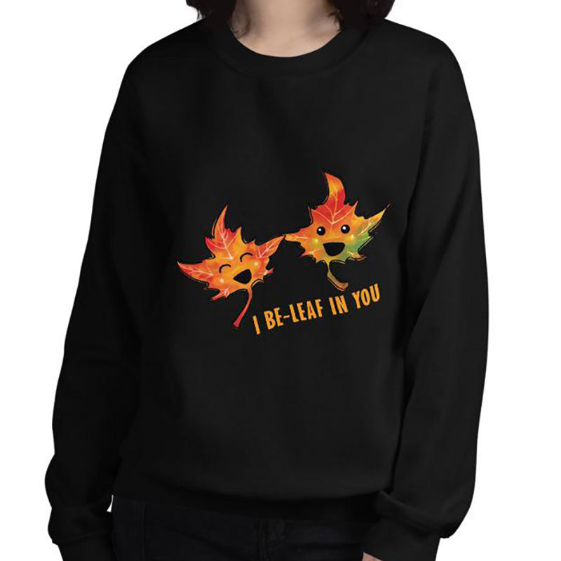 "A woman is wearing a unisex sweatshirt in the colour black, featuring art of two smiling maple leaves with the words, ""I Be-Leaf In You"""