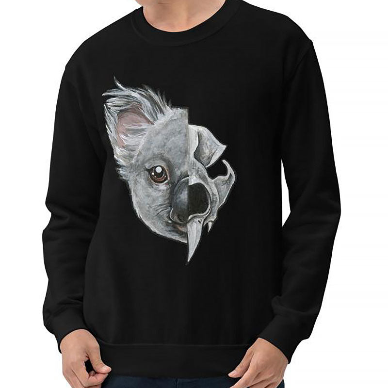 A man is wearing a unisex sweatshirt in the colour black, printed with an illustration split into two: the left side features the face of a koala bear, and the right side features an evil looking koala skull.
