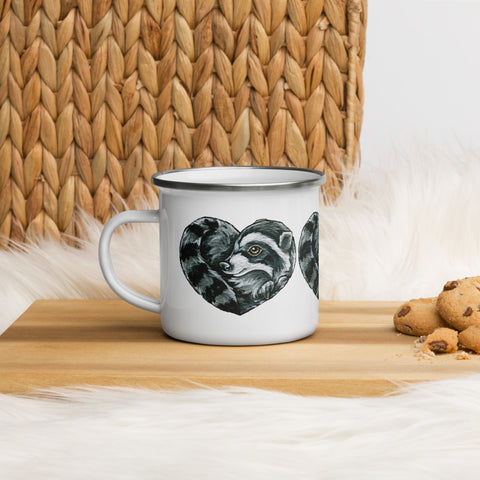 A 12 oz white enamel mug with silver rim, printed with art of a raccoon, curled up in the shape of a heart.