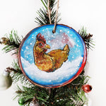 A Christmas ornament with a painting of a chicken, sitting on snow as snowflakes fall. The ornament is painted in blues and reds.