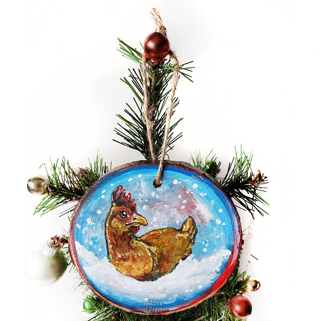 A holiday ornament with art of a chicken, sitting on snow as snowflakes fall. The ornament is painted in blues and reds.