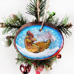 A holiday ornament with artwork of a chicken, sitting on snow as snowflakes fall. The ornament is painted in blues and reds.