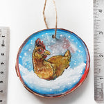 A wood ornament, painted with a chicken, next to two rulers to show size: 2 7/8 x 3 1/8 inches or 7.3 x 8 cm