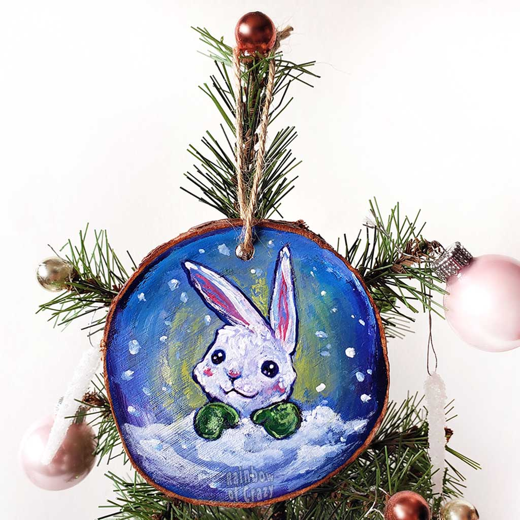 A wood Christmas ornament features art of a white rabbit, peeking out from behind the snow, wearing green mittens.