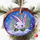 A holiday ornament, painted on a wood slice, features art of a white rabbit, peeking out from behind the snow, wearing green mittens.