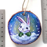 A Christmas ornament with a painting of a white rabbit with green mittens, painted on a wood slice, is displayed next to two rulers to show its size: 2 15/16 x 2 15/16 inches or 7.5 x 7.5 cm,