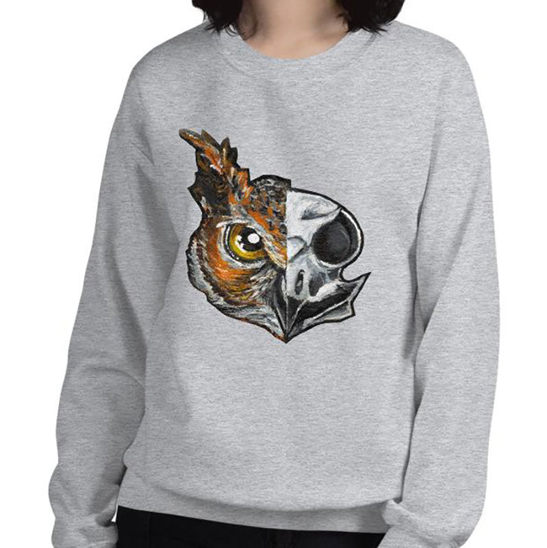 A woman wears a unisex sweatshirt in the colour sport grey, printed with artwork of a split image: the left side features an owl's face, and the right side features an evil looking owl skull.
