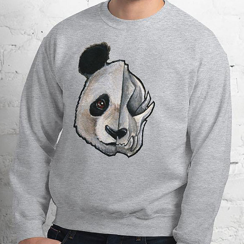 A man wears a unisex sweatshirt in the colour sport grey, printed with artwork of a split image: the left side features an panda's face, and the right side features an evil looking panda skull.