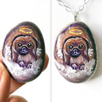 A portrait painting of a Pekingese dog as an angel with wings, painted on a small rock, available as a keepsake or pendant necklace