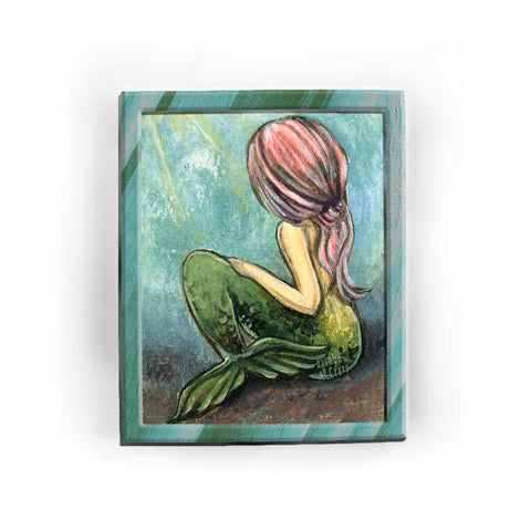 An art print of a mermaid sitting on the ocean floor, looking away from the viewere, as long pink hair flows down her back
