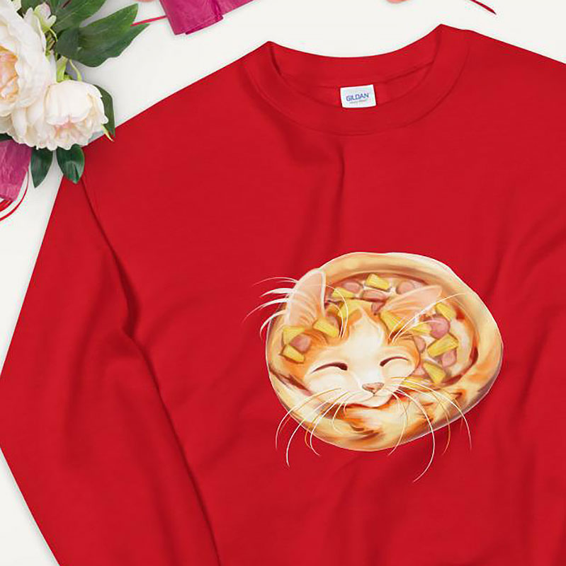 A unisex sweatshirt in the colour red, printed with art of an orange cat as a pineapple pizza, topped with pineapple and ham.