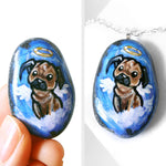 "Named ""Bug the Pug"", a beach rock is painted with dog art of a pug as an angel, available as either a keepsake gift of pendant necklace"