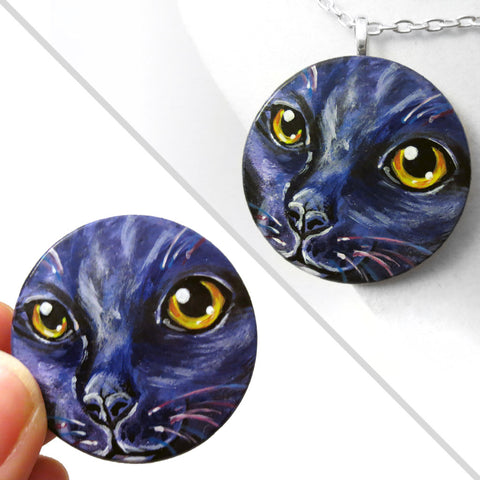 A wooden disc is painted with a cat's face in dark purple and black with yellow and orange eyes, available as a keepsake or pendant necklace