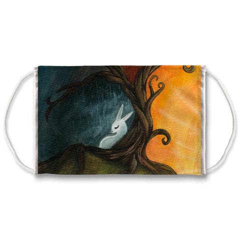 White reusable face mask features a print of a white rabbit under the Tree of Life. One side is dark and rainy, while the other is sunny and bright.