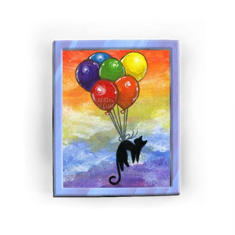 An art print featuring an illustration of a black cat, floating through rainbow coloured skies while tied to 6 balloons, each a separate colour of the rainbow