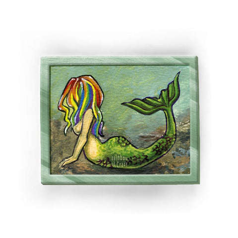 An art print of a mermaid with long, flowing rainbow hair, lying on her stomach on the ocean floor.