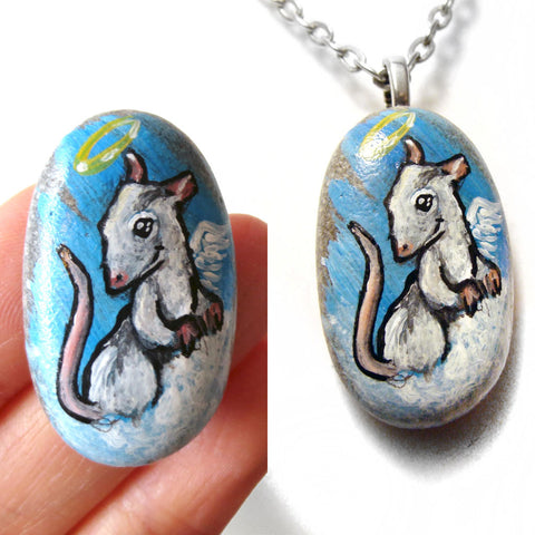 a pet portrait of a white and grey rat as an angel on clouds, painted on a beach rock. available as a beach stone or a pendant necklace