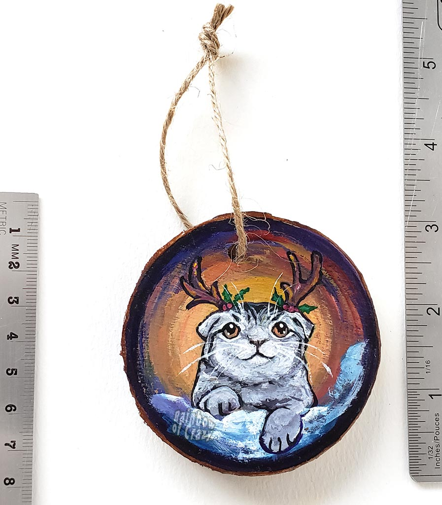A wood Christmas ornament, hand painted with a portrait of a Scottish fold cat with reindeer antlers, sitting on the snow.