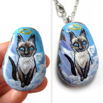 art of a siamese cat as an angel, is hand painted on a river rock, and is available as either a keepsake or a pendant necklace