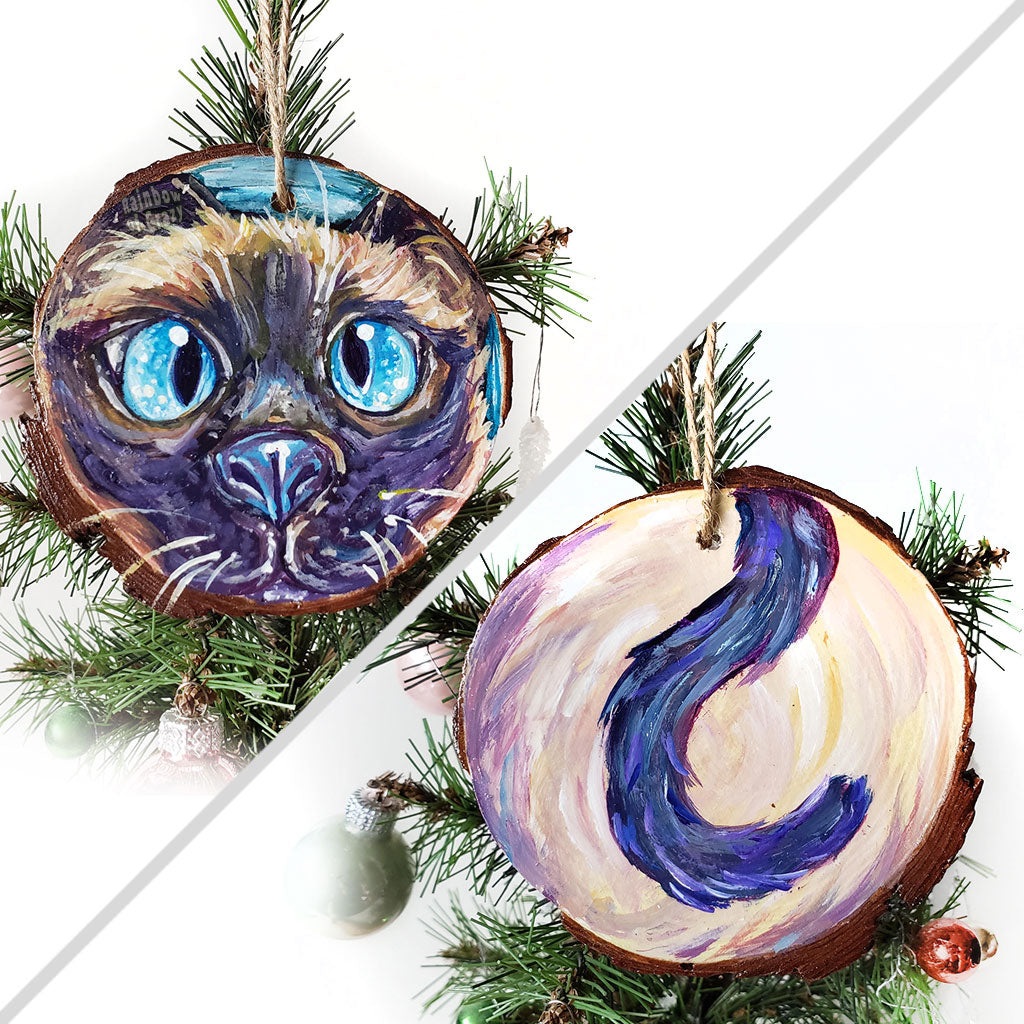 A wood ornament featuring art of a siamese cat's face with blue eyes, and it's tail on the back.